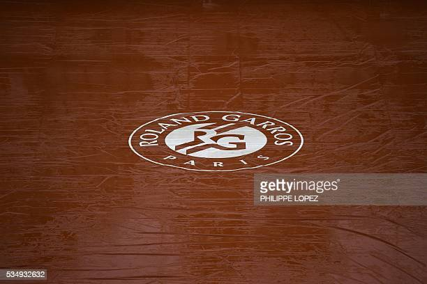 A photo taken on May 28 2016 shows the Roland Garros logo on a tarp covering the court after rain interrupted play during the women's third round...