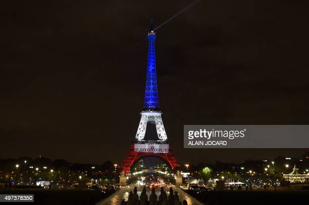A photo taken on November 16 2015 in Paris shows the Eiffel Tower illuminated with the colors of the French flag in tribute to the victims of the...