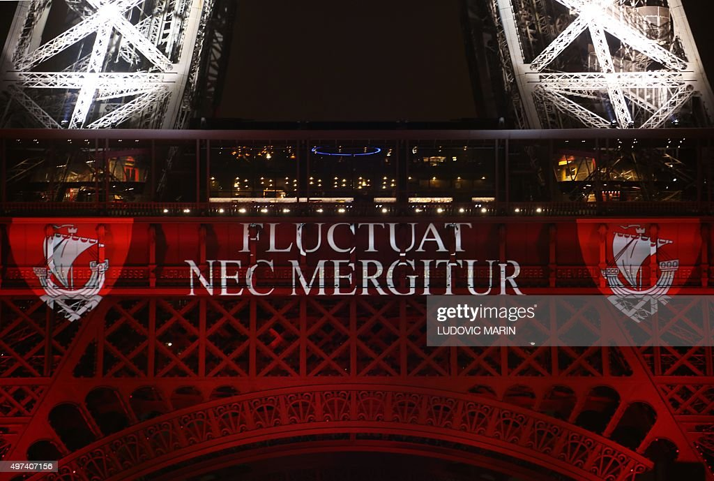 A photo taken on November 16 2015 in Paris shows the motto of the city of Paris written on the side on an Eiffel Tower illuminated in colors of the...