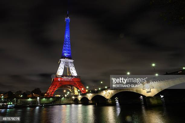 A photo taken on November 17 2015 in Paris shows the Eiffel Tower illuminated with the French national colors in tribute to the victims of the...