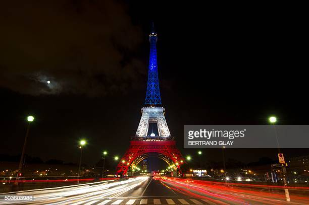 A photo taken on November 17 2015 in Paris shows the Eiffel Tower illuminated with the colors of the French national flag in tribute to the victims...