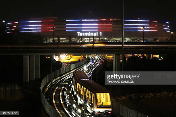 A photo taken on November 17 shows the Roissy Airport Terminal 1 illuminated with the colours of the French national flag in tribute to the victims...