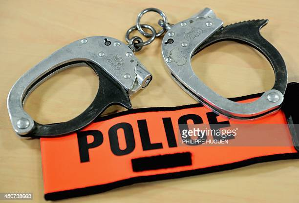 A photo taken on November 20 2013 shows handcuffs and a police badge at a police station in the northern French city of Arras AFP PHOTO / PHILIPPE...