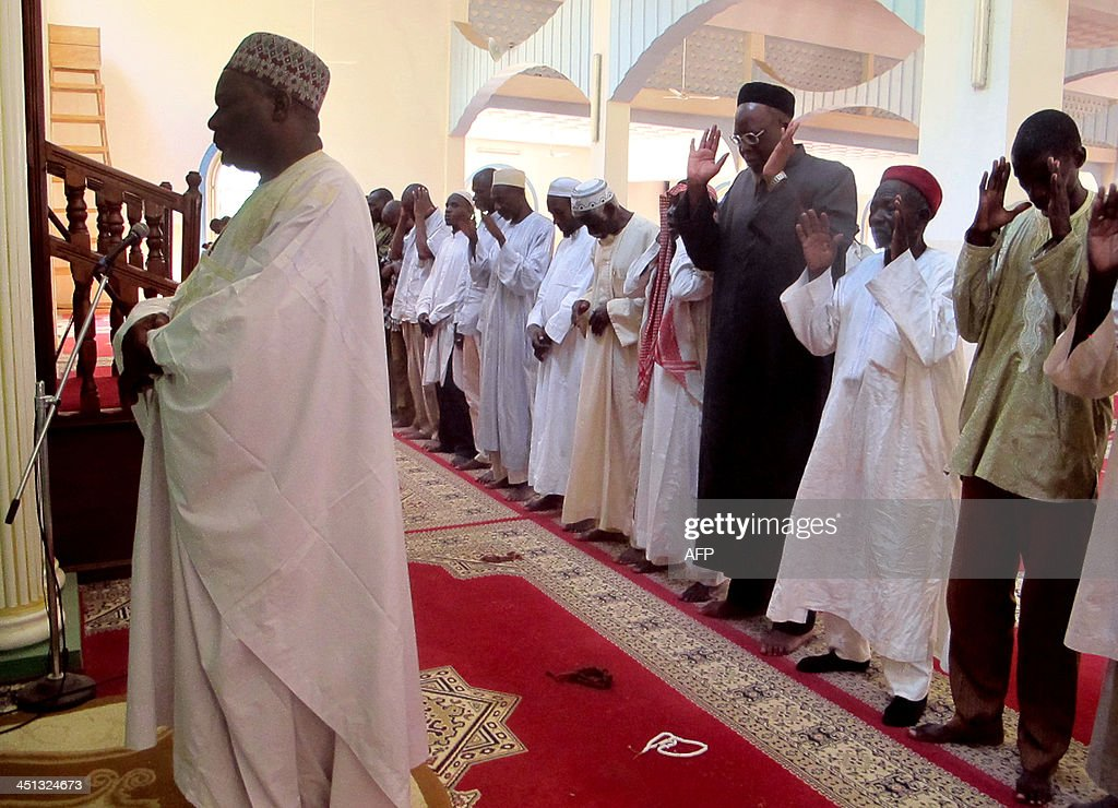 A photo taken on November 20, 2013 shows Imam Dalil Hayatou (L), leading the prayers at the Great Mosque in Maroua's Dougoi district, northern Cameroon. AFP PHOTO / REINNIER KAZE