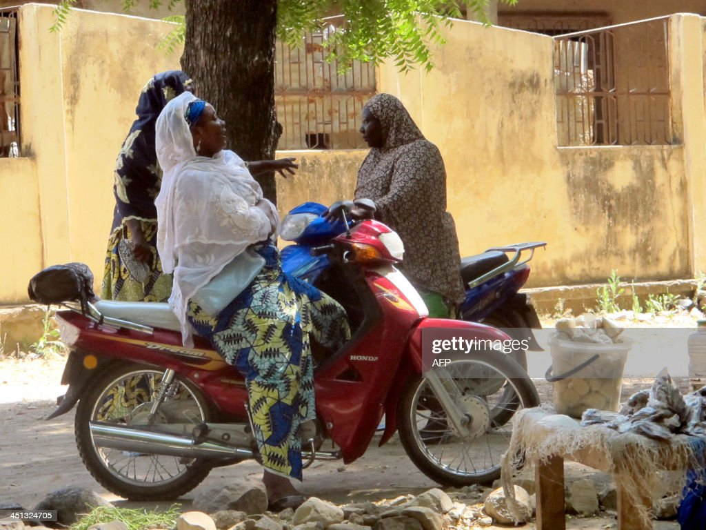 A photo taken on November 20, 2013 shows women chatting while sitting on their bikes in a district of Maroua, northern Cameroon.
