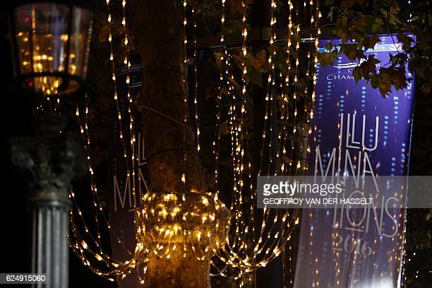 A photo taken on November 21 2016 shows a banner for 'Illuminations 2016' after the Christmas lights of the Champs Elysees avenue in Paris were...