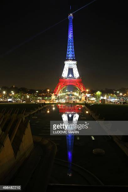 A photo taken on November 23 2015 in Paris shows the reflection of the Eiffel Tower illuminated in the colours of the French tricolour flag in...
