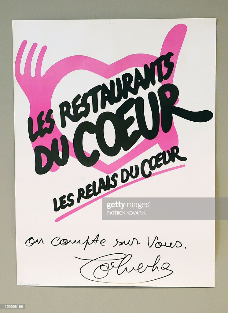 A photo taken on November 26, 2012 in Paris shows a poster displaying the logo of the French charitable organisation 'Les Restos du Coeur' (Restaurants of the Heart) during the launching of the 28th winter campaign to distribute food to the needy .