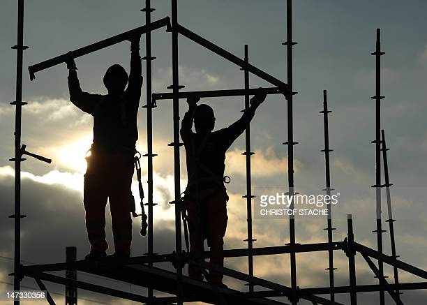 Photo taken on November 28 2011 shows two men standing on a scaffolding during construction works near the small Bavarian village Germering near...