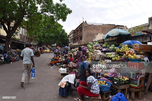 A photo taken on November 6 2014 shows fruit and vegetable sellers at a market in Ouagadougou Burkina Faso Burkina Faso's armyappointed leader on...