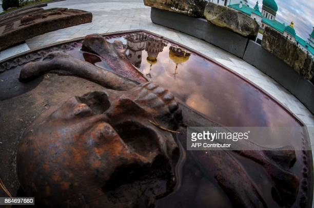 A photo taken on October 21 2017 shows an old tombstone reflecting the golden domes of the New Jerusalem Orthodox Monastery outside the town of Istra...