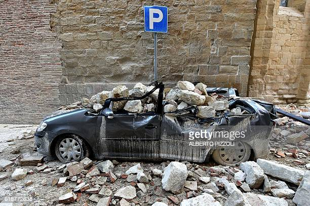 TOPSHOT A photo taken on October 28 2016 shows a damaged car in the 'red zone' an area cordoned off for safety reasons in Camerino where 80 per cent...