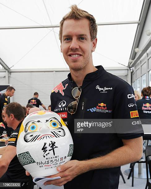 A photo taken on Octoer 6 20111 shows Red BullRenault driver Sebastian Vettel of Germany as he holds a 'Dharma doll' prestented to him by Japanese...