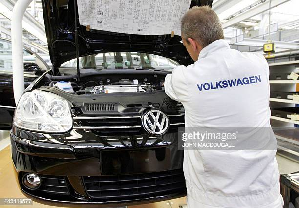 A photo taken on September 21 2005 shows a worker checking a Volkswagen Golf model on a production line at VW's headquarters and main manufacturing...