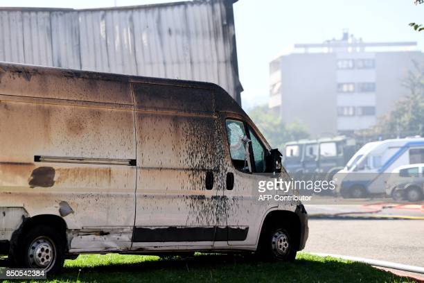 A photo taken on September 21 2017 in Grenoble eastern France shows a damaged vehicle after an arson devastated a hangar of the French gendarmerie...