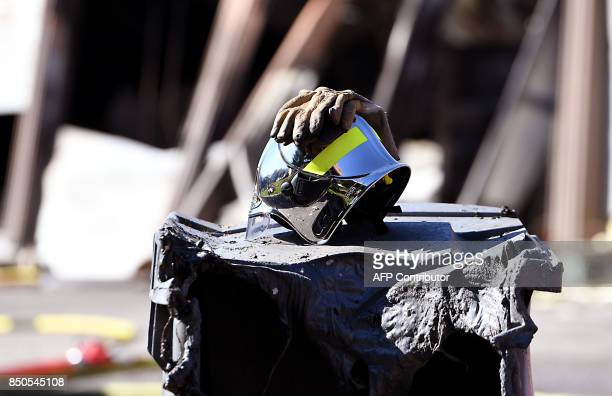 A photo taken on September 21 2017 in Grenoble eastern France shows a glove and helmet of a firefighter a day after a hangar of the French...