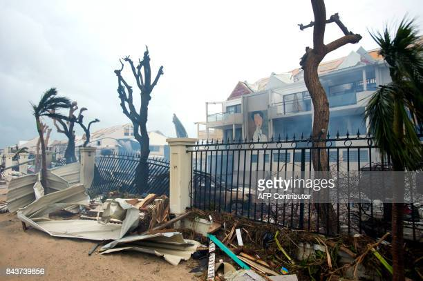 A photo taken on September 6 2017 shows smoke rising from a fire near debris and damaged buildings in Marigot near the Bay of Nettle on the French...