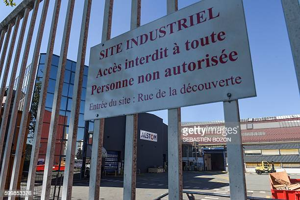 A photo taken on September 7 shows a board reading 'industrial site entrance forbidden to all people not authorised' on a fence in front of the logo...