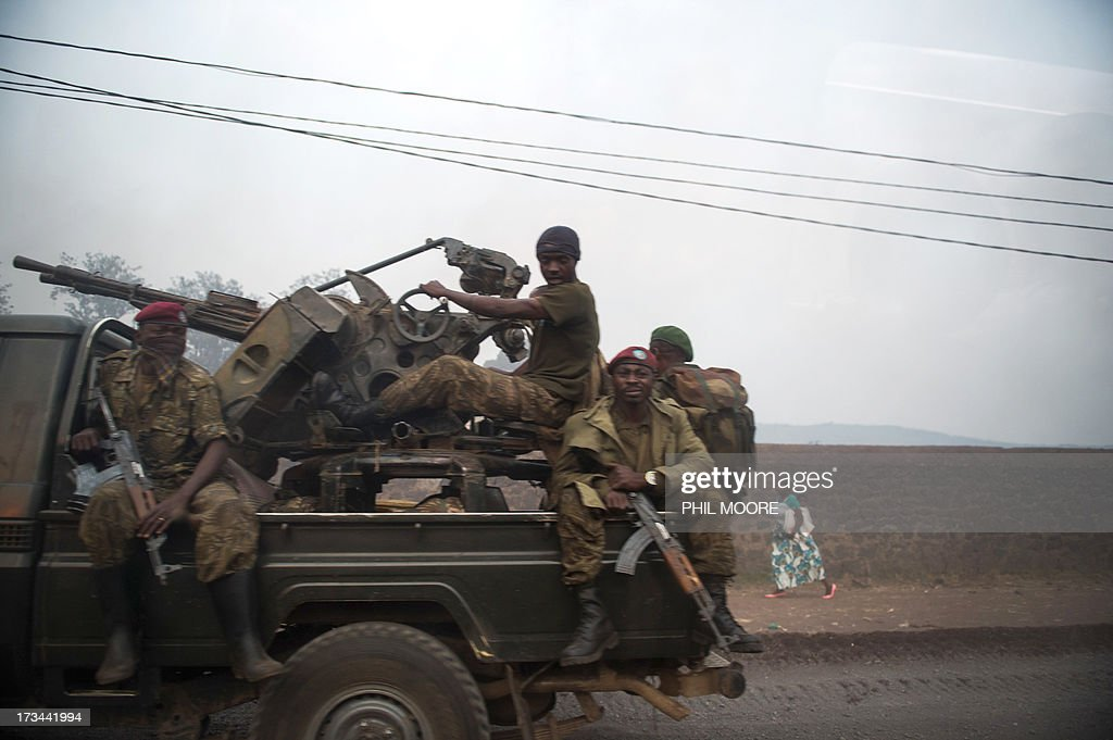 Photo taken through a car window shows a group of Congolese army soldiers driving out of Goma in the east of the Democratic Republic of the Congo on July 14, 2013. Exchanges of artillery and rocket-fire broke out today between the Congolese army and M23 rebels, with impact visible from Kanyarucinya in the foot-hills of the Nyiragonga volcano. More than 55,000 refugees from eastern Democratic Republic of Congo have arrived in Uganda after fleeing a rebel attack, Red Cross officials said July 14, although the rate of new arrivals has begun to slow down. AFP PHOTO / PHIL MOORE