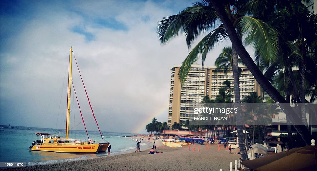 A photo taken with a cell phone shows a general view shows Waikiki Beach with a rainbow in the background on January 3, 2013 in Honolulu, Hawaii. US President Barack Obama returned to Hawaii on January 2, to continue his vacation after dealing with the 'fiscal cliff' crisis. AFP PHOTO/MANDEL NGAN