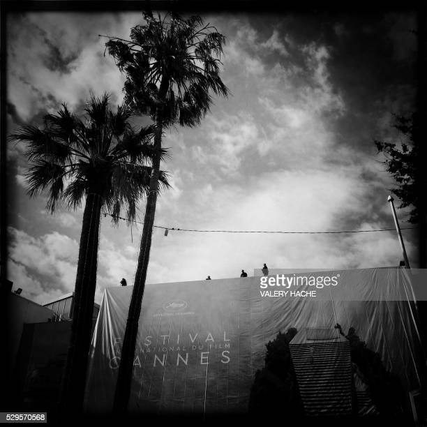 A photo taken with a mobile phone shows workers set up a banner of the official poster of the 69th Cannes' film festival on May 9 2016 on the...
