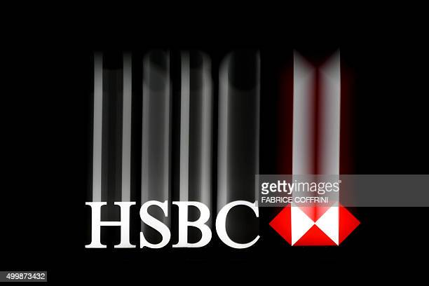 A photo taken with a slow speed exposure on late December 2 2015 in Geneva shows a sign of HSBC banking giant on the top of a branch / AFP / FABRICE...