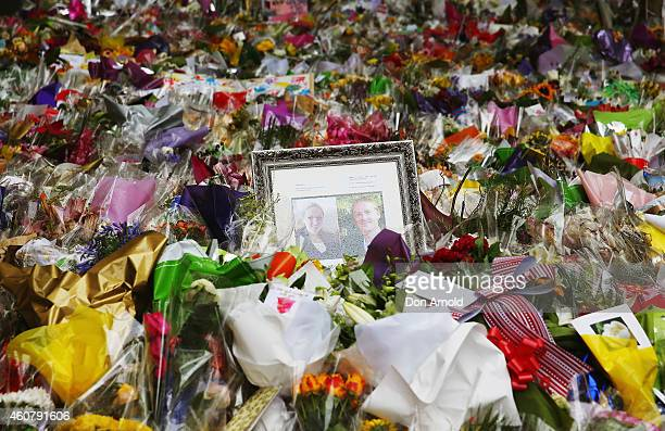 A photo tribute to Tori Johnson and Katrina Dawson is seen amongst the flowers at Martin Place on December 23 2014 in Sydney Australia Volunteers...