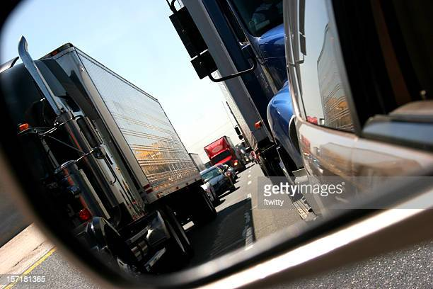Photo view in rearview mirror trucks in traffic on roadway