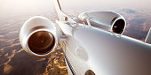 Photo of White Luxury Generic Design Private Jet Flying in Blue Sky at sunrise.Closeup Picture of two Reactive Turbine.Mans world.Full power.Business Travel Picture.Horizontal,Film Effect.3D rendering
