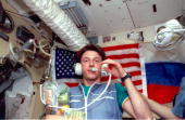 Astronaut C Michael Foale wearing Mir communications systems headset onboard Russia's Mir Space Station's Base Block is pictured with fruit from...