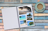 Photobook Album on Wooden Floor Table with Travel Photos of beaches and Coffee or Tea in Cup