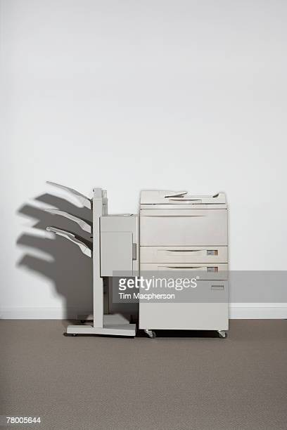 A photocopier against a white wall.