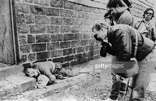 Photograph and cameraman take pictures on March 20 1988 of a Kurdish father holding his baby in his arms in Halabja northeastern Iraq Both were...