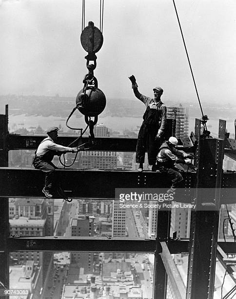 The picture shows members of a derrick gang fixing a beam during the construction of the Empire State Building showing the streets of New York far...