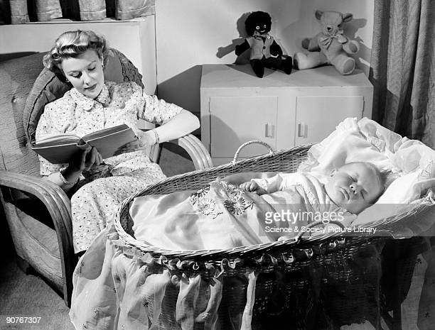 A photograph by Photographic Advertising Limited A mother sits in an armchair as her baby sleeps in a cot in the foreground Toys in the background...