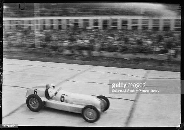 Photograph by Zoltan Glass Car No 6 a MercedesBenz W25 GP being driven by Rudolf Caracciola along the front of the pits