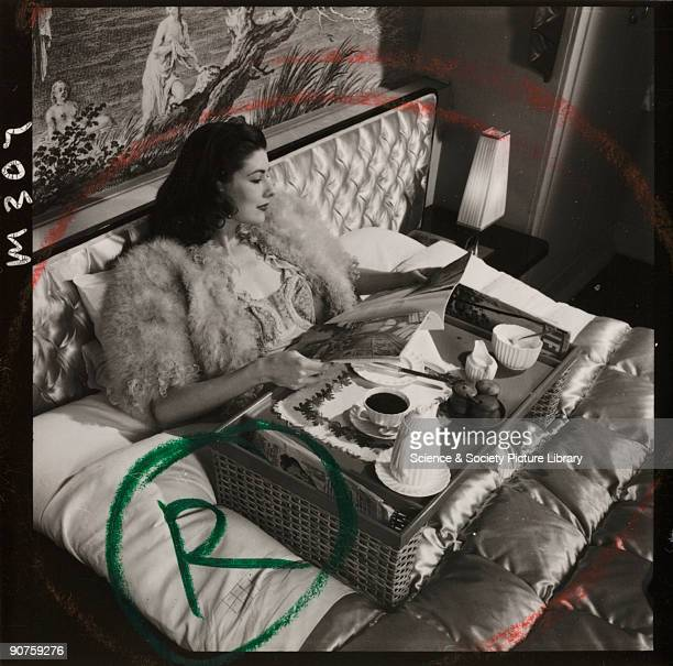 Photograph by Zoltan Glass of a model wearing a mohair or feather bed jacket reading a magazine with her morning coffee on a tray