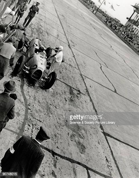 Photograph by Zoltan Glass Racing driver Auguste Momberger and mechanics preparing a racing car during a pit stop He was driving car No 2 an...