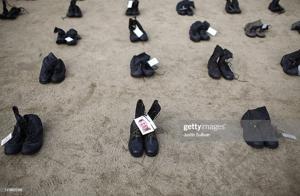 A photograph is displayed on a pair of combat boots that are part of the 'Eyes Wide Open' exhibit in front of San Francisco City Hall on March 19, 2012 in San Francisco, California. The Eyes Wide Open exhibition includes a pair of boots for every one of the 481 California servicemen and women who died in the Iraq war.