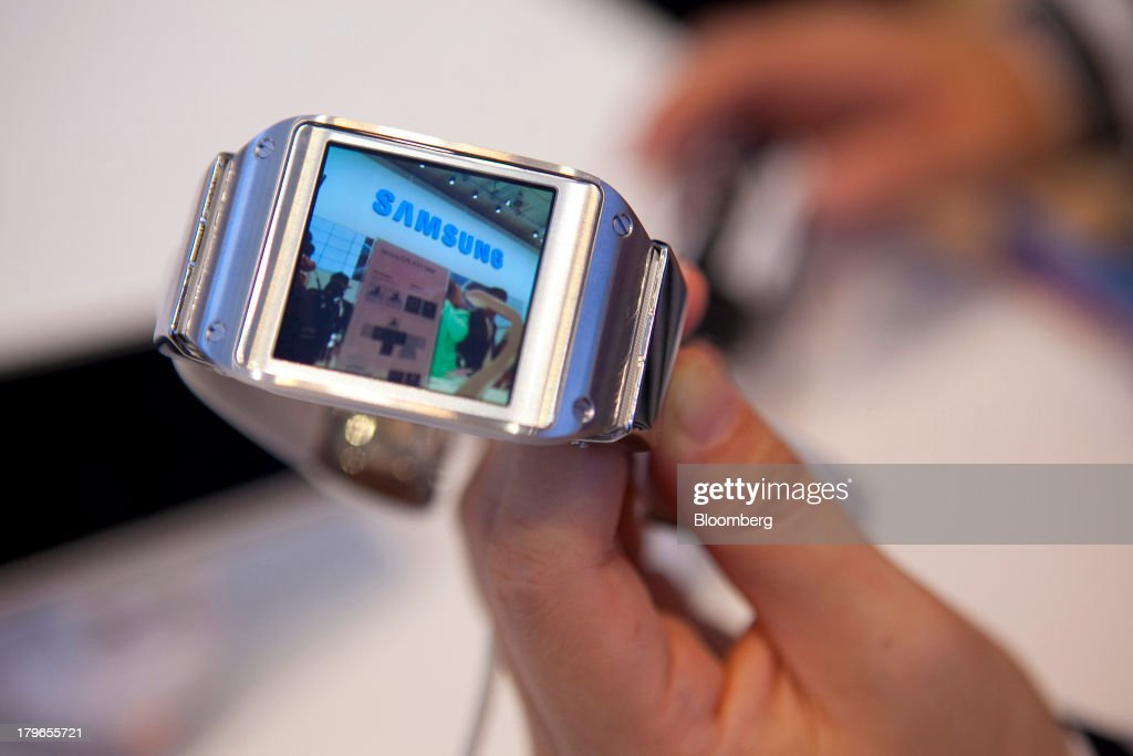 A photograph is displayed on the screen of a Galaxy Gear smart watch device, manufactured by Samsung Electronics Co., in this arranged photograph at the IFA consumer electronics show in Berlin, Germany, on Friday, Sept. 6, 2013. Global smartphone revenue will rise 22 percent in 2013, or nearly half the pace of an expected 41 percent gain in shipments, amid falling prices, according to UBS. Photographer: Krisztian Bocsi/Bloomberg via Getty Images