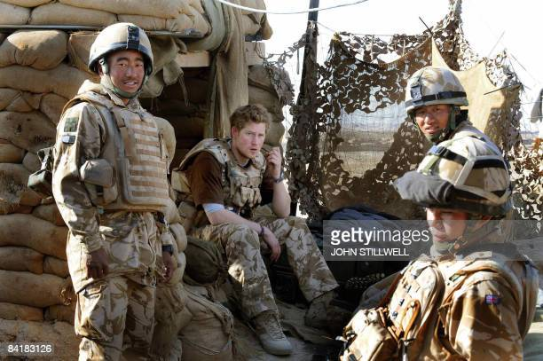 A photograph made available on February 28 shows Britain's Prince Harry as he sits with a group of Gurkha soldiers after firing a machine gun from...