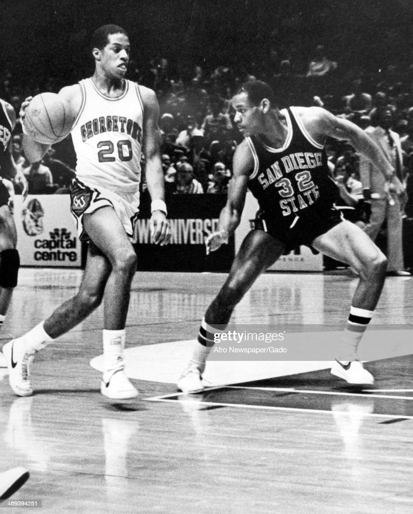 A photograph of a basketball match of the Georgetown Hoyas vs San Diego Aztecs with San Diego's Zack Jones no 32 attempting to cut off Georgetown's...