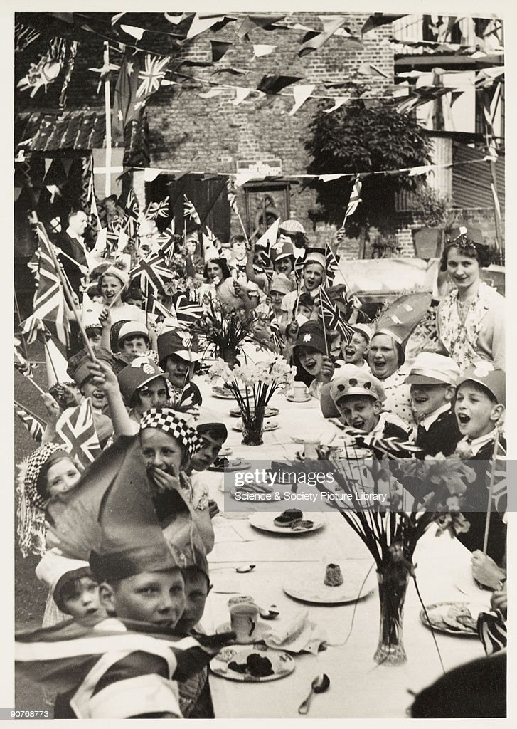 A photograph of a children's Coronation tea party in Chiswick, London, taken by an unknown photographer in May 1937. This photograph is from an album compiled by Kodak Limited to record the Coronation of King George VI (1895-1952) and Queen Elizabeth (1900-2002) on 12 May 1937. George VI was the second son of George V and Mary of Teck. In 1923 he married Lady Elizabeth Bowes-Lyon, who bore him two daughters, Elizabeth (Queen Elizabeth II) and Margaret. He died from cancer on 6 February, 1952.