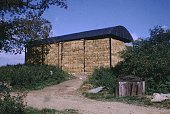 A photograph of a covered building with no sides used to store bales of hay the bales are stacked several stories high the building is situated on a...