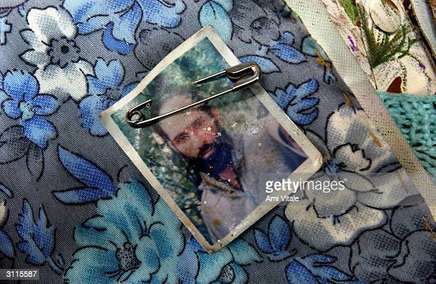A photograph of a Kashmiri man who disappeared is pinned to the shirt of his wife during a protest of Association of Parents of Disappeared Persons...