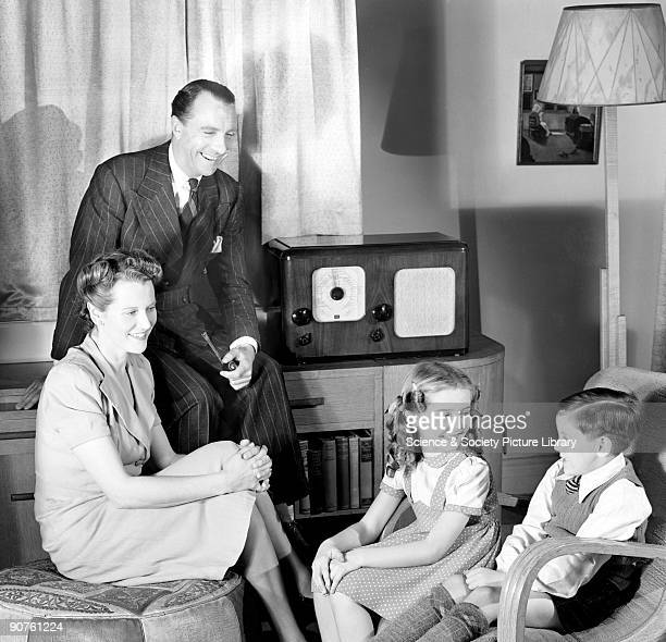 A photograph of a laughing family group of husband wife and two children in their living room taken for Photographic Advertising Limited in 1948...