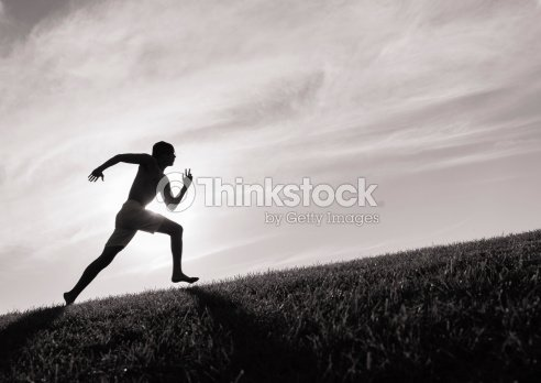 Photograph of a man in silhouette running up a hill : Stock Photo