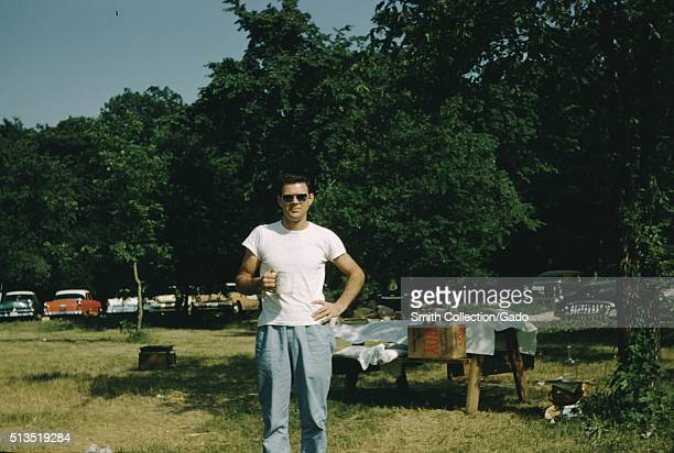 A photograph of a man posing with a mug the man is wearing a white tshirt and blue slacks behind him a picnic table can be seen covered in a cloth...