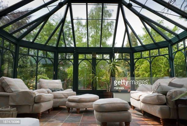 A photograph of a modern conservatory with brown furniture