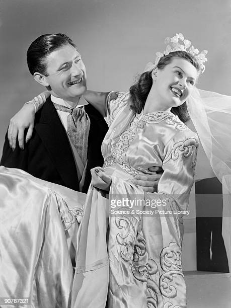 A photograph of a smiling groom carrying his bride across the threshold taken by Photographic Advertising Limited in 1949 Romantic images proved...